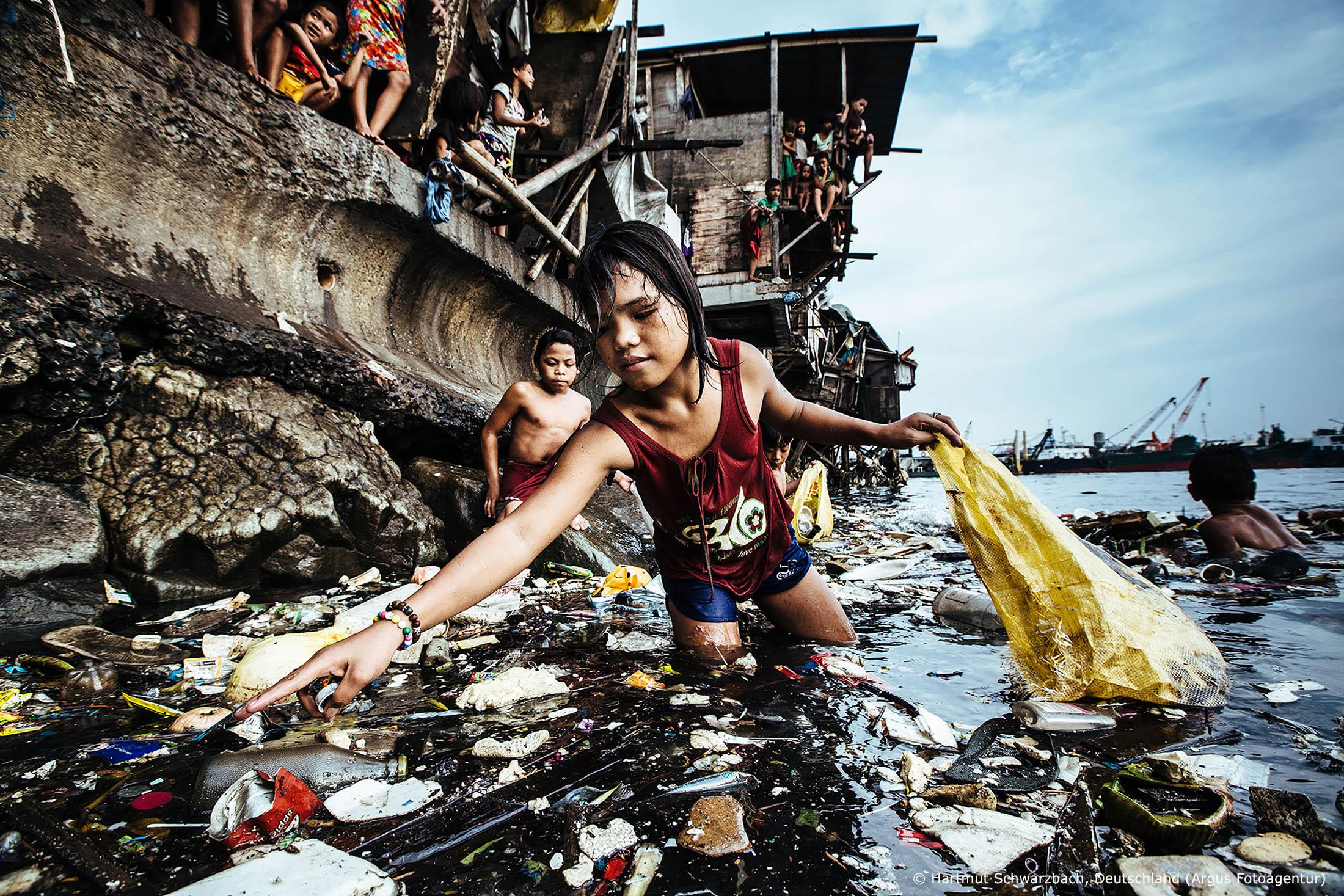 1. Preis 2019: Hartmut Schwarzbach (Deutschland), Argus Fotoagentur, »Philippinen: Die Kinder, der Müll und der Tod« Nur Ratten gefällt es hier. Im Stadtteil Tondo am Hafen von Manila leben Kinder davon, Plastikflaschen aus der verdreckten Bucht zu fischen, um sie bei einem Müll-Recycler zu verkaufen. Wenn sie Glück haben, liegt ihr Tageslohn bei 50 philippinischen Pesos, 90 Cents. Kinderarbeit ist auch auf den Philippinen verboten, aber im Slum von Tondo, dem größten des Landes, ist das nicht mehr als ein unbeachtetes Gesetz. Hier, wo 70.000 Einwohner auf einem Quadratkilometer in Hütten aus Wellblech, Pappe und Restholz hausen, ohne Strom und Trinkwasseranschluss; wo Dengue und Durchfallerkrankungen, Leptospirose und Hautkrankheiten grassieren, wo Mangelernährung verbreitet und die Lebenserwartung niedrig ist, müssen auch Kinder ein bisschen Geld verdienen. Mädchen wie die dreizehnjährige Wenie Mahiya auf diesem Bild, aber auch schon Zehnjährige, Siebenjährige. Mitunter paddeln sie auf Bambusflößen oder Kühlschranktüren durch das Schmutzwasser der Bucht, ein vor allem in der Taifunzeit lebensgefährliches Unterfangen. Aber gestorben wird hier auch, wie der deutsche Fotograf Hartmut Schwarzbach erfahren musste, an Lebensmittelvergiftungen. Nackte Armut, Kinderarbeit und die Müllflut in den Meeren: Schwarzbach dokumentiert in seinen eindringlichen Fotos von Tondo das Zusammentreffen gleich dreier Katastrophen.